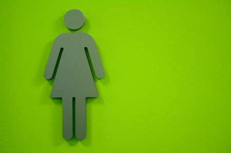 bathroom sign: Ladies bathroom sign with green background .