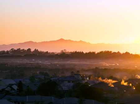 Morning sunrise beautiful winter golden light and fog over the suburbs of Rototuna and Flagstaff in the city of Hamilton New Zealand with Mount Te Aroha in the background