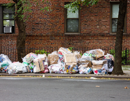 Queens, NY: August 30th 2014 Typical street scene with residential trash piling-up and sits on the sidewalk awaiting pickup from the city waste management company
