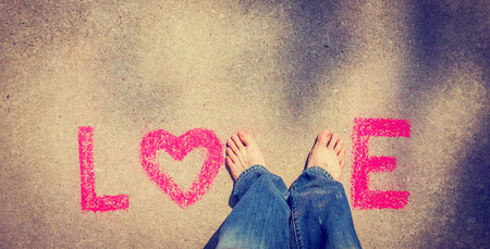 abstract love written with chalk and bare feet with retro filter shallow depth of field