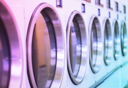 oversize load: laundromat machine washer line with closed doors shallow depth Stock Photo