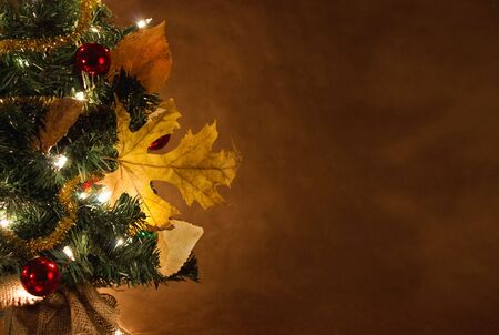 miniture christmas tree decorated with fall leaves shallow depth of field Reklamní fotografie
