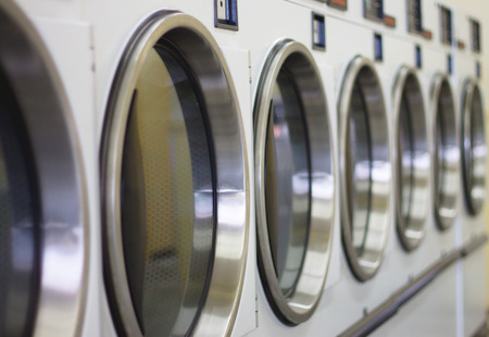 laundromat machine washer line with closed doors shallow depth of field