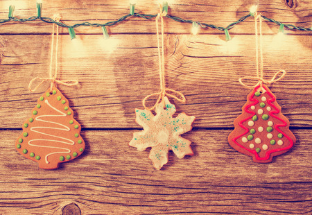 gingerbread cookies hanging with worn wooden background with christmas lights illuminated with retro instagram filter Reklamní fotografie