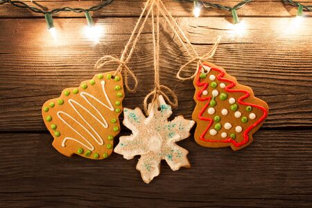 gingerbread cookies hanging with worn wooden background with christmas lights illuminated