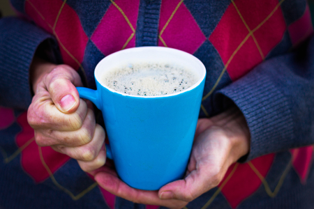 woman holding a cup of coffee in her hands with her retro sweater as the background Reklamní fotografie