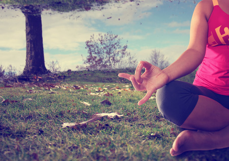 concept of woman doing yoga lotus pose anywhere, even when the sky is a mess with a retro instagram filter shallow depth of field