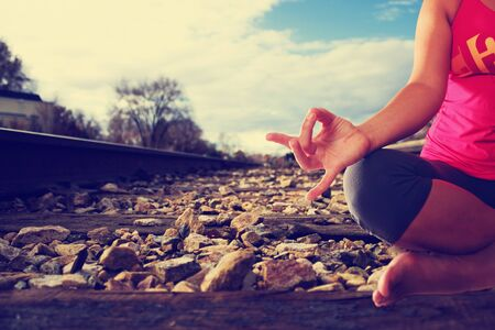 concept of woman doing yoga lotus pose anywhere, even on train tracks with retro instagram filter shallow depth of field