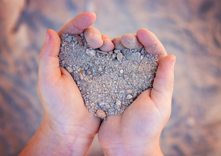 young girl holding gravel in shape of heart shallow depth of field Reklamní fotografie