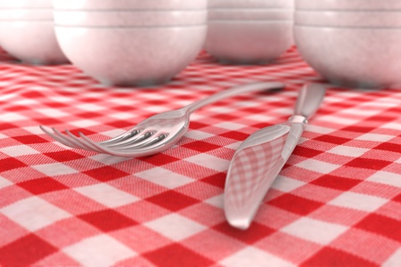 fork and knife closeup on a red table cloth with dashware behind photo