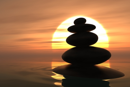Zen pebbles stacked into the water with sunset on the background photo