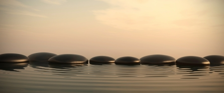 Zen stones into the water with sunrise on the background photo