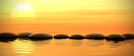 Zen stones into the water with sunset on the background photo