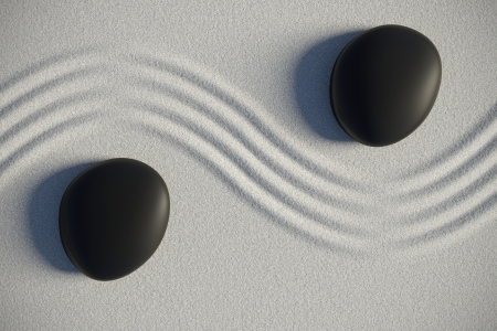 Zen garden on sand with two black stones separated by a drawing ripples 스톡 콘텐츠