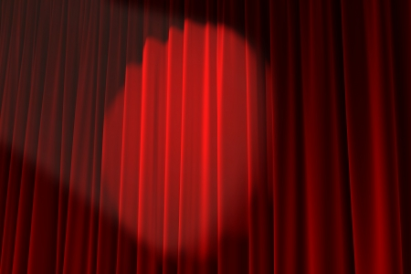 A spotlight lights up a red curtain stage