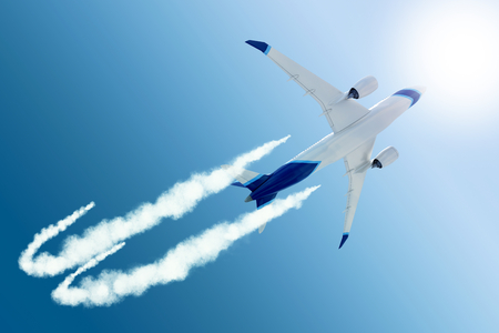 A bottom view of a white and blue airplane traveling in a sunny sky creating a white contrail