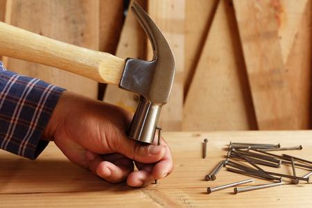 Hammer schlägt auf den Finger Schlagen Sie nicht auf die Nägel Standard-Bild