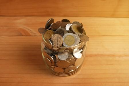 Saving money Coins In a glass bottle on wooden floor Stock fotó