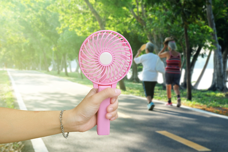 Hand holding pink portable fan at the public park in summer, hot weather Фото со стока