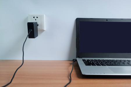 Podłącz przewód zasilacza do gniazdka elektrycznego na białej ścianie laptopa na drewnianej podłodze