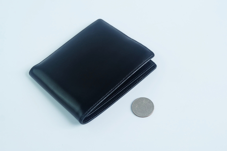 Black leather wallet with 5 baht coins on white background, Insufficient expenditure poverty concept.