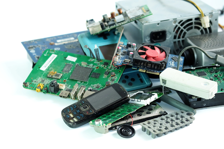 Pile de déchets électroniques, carte de circuit informatique, téléphone portable, cassé ou endommagé, sur fond blanc.