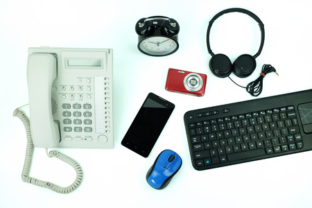 White office landline telephone and smartphone, Keyboard computer and table clock Used modern Electronic gadgets for daily use isolated on white background, Top view.