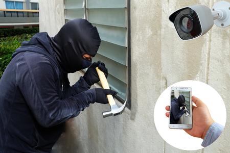 La caméra de surveillance capture et enregistre un voleur masqué avec un marteau et une main tenant la détection de téléphone portable sur l'application, système de sécurité domestique