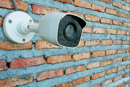 Closeup Surveillance Camera or cctv of security on newly built red brick wall texture background 免版税图像