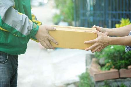 Delivery man staff in the colorful jacket uniform holds parcel box that is about to be delivered to customer with blurred background