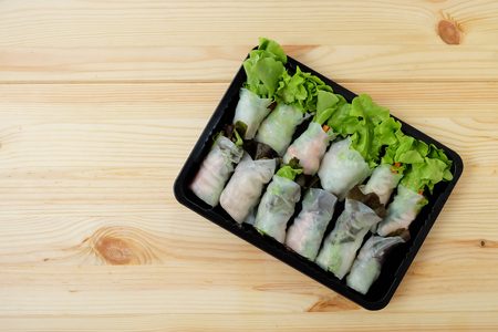 Roll salad Green oak and red oak fresh vegetables in a black plastic box on a wooden floor.Top view, with copy space