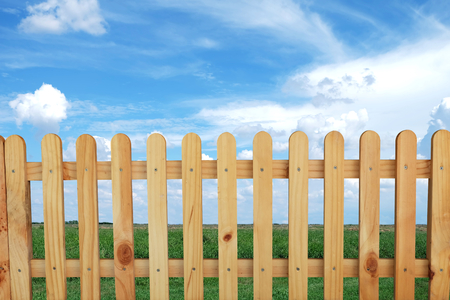 Beautiful wooden fence, green fields and blue sky background Imagens