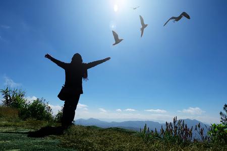 Touristenfrau in einem Pullover, der auf der Klippe steht, mit erhobenen Händen und Blick auf Himmel und Berge mit fliegenden Möwen, Freiheits- und Friedenskonzept Standard-Bild