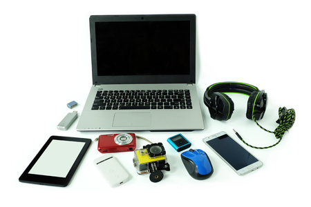 Desk with gadgets or electronic equipment for daily use, laptop computer, cell phones and digital camera isolated on white background