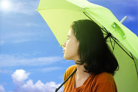 Cute asian woman holding umbrella with sunlight and blue sky and Cloud background in the hot weather In summer