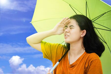 Cute asian women use their hands to covers her face from the sun and holding umbrella with sunlight and blue sky and Cloud background in the hot weather In summer