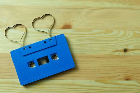 Blue cassette tape audio with label tape ribbon heart shape on wooden floors with Copy space, Valentine day The lovers are together concept. Imagens