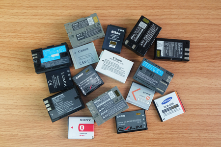 BANGKOK, THAILAND - September 14, 2018 : Used battery for compact camera and dslr in many brands on wooden background