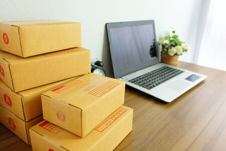 Laptop computer and Product Box or shipping parcel box on a wooden table, Online shopping, work at home, e commerce.