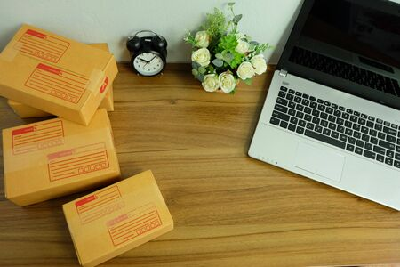 Laptop computer and Product Boxs or shipping parcel box on wooden table, Online shopping, work at home, e commerce.