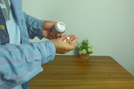 Man holding White pills and medicine bottles, paracetamol, Headache medicine Vitamin And Dietary Supplements Concept