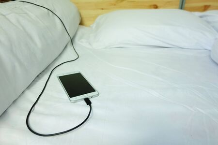 Smart phone is charging is plugged on the white bed, The danger of charging electricity when sleeping.