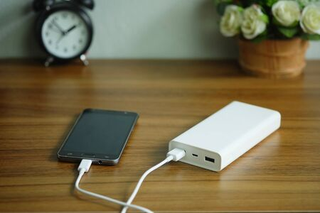 Smartphone is charging with backup battery or Power bank on the desk wooden table.