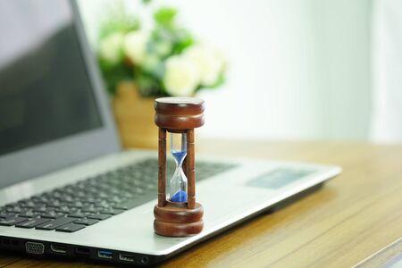 Sablier en bois sur un ordinateur portable, gestion du temps et du concept de compte à rebours jusqu'à la date limite