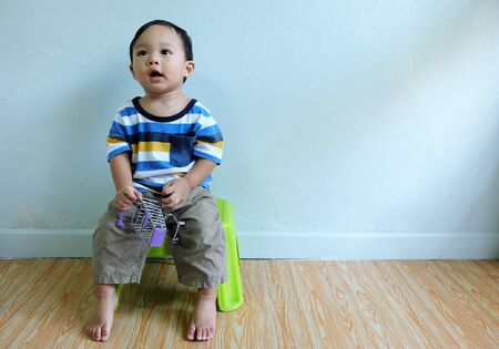 Happy little cute asian boy is wearing colorful shirt sitting on a chair smiled and laughed in living room Stock fotó