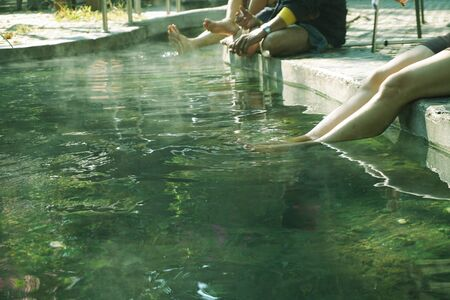 Women and people stretch their legs and feet soaked in hot mineral spring water. Health and relaxation activities at Sankampang Hot Springs, Chiang Mai, Thailand. Standard-Bild
