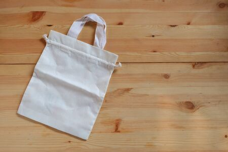 Empty white canvas cloth bag on wooden floor, Replace plastic bags with eco friendly products and to reduce waste, Zero waste, Global warming concept Stock Photo