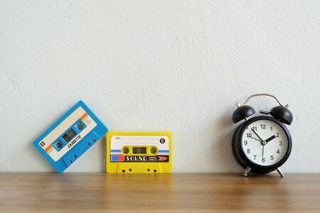 Old colorful cassette tape with an alarm clock on a wooden table and leave blank space above for text input