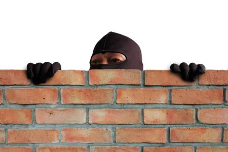 Masked thief is climbing the wall to steal property in the house, Detecting CCTV camera surveillance of home security systems. 스톡 콘텐츠 - 139937758