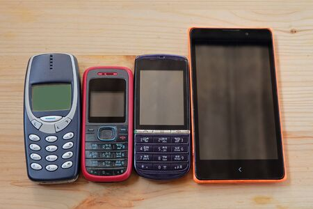 Old used mobile phones on wooden floors, E-waste is a problem with environmental concepts should be reused and recycle. 에디토리얼